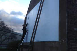 A person on a ladder paints the side of a building