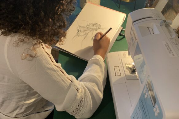 Tanica sits drawing next to a sewing machine