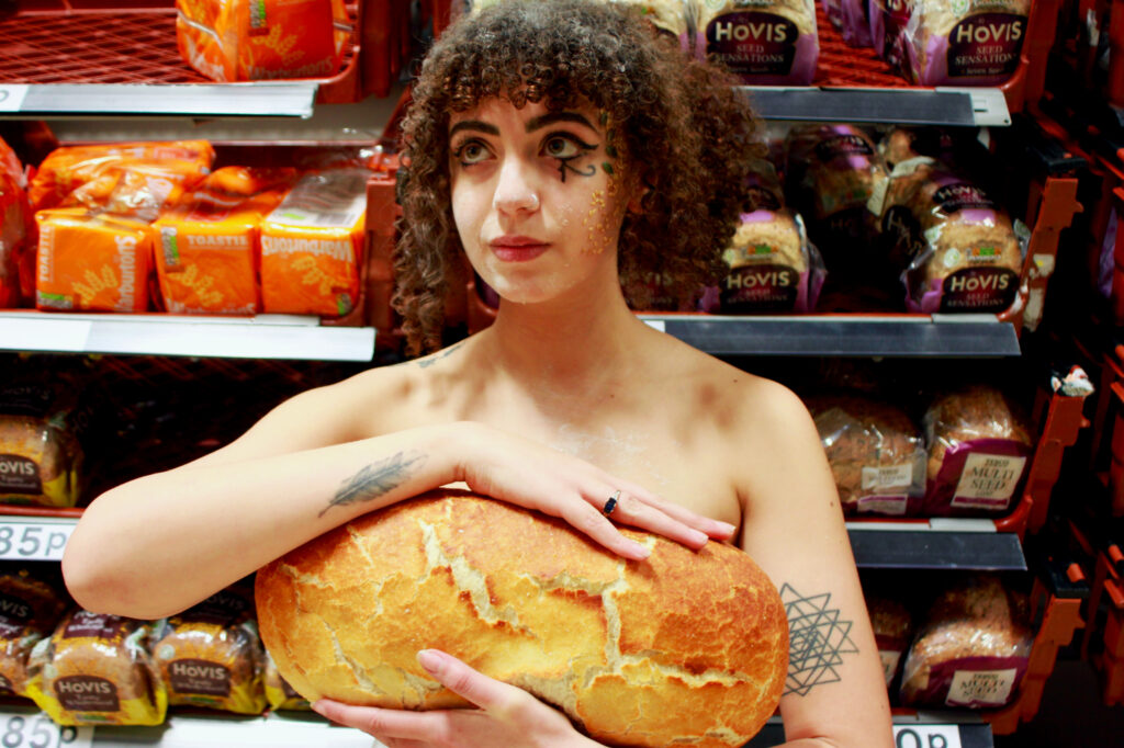 Arist Miray Sidhom stands in front of shelves of bread, holding a large gold loaf