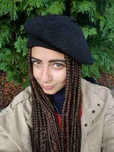 A photo of Miray Sidhom, wearing a black beret with braided hair and a beige coat, against a green leafy background
