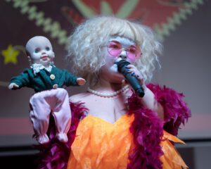 Artist Tammy Reynolds, wearing red and orange (with pink sunglasses) holds a microphone and a doll