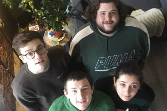 Three men and a women dressed in green look up at the camera.