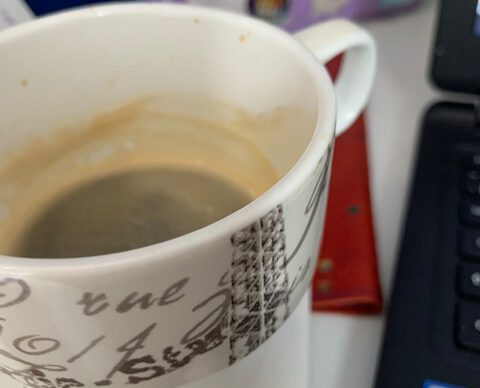 A cup of coffee with a barbie bag in the background