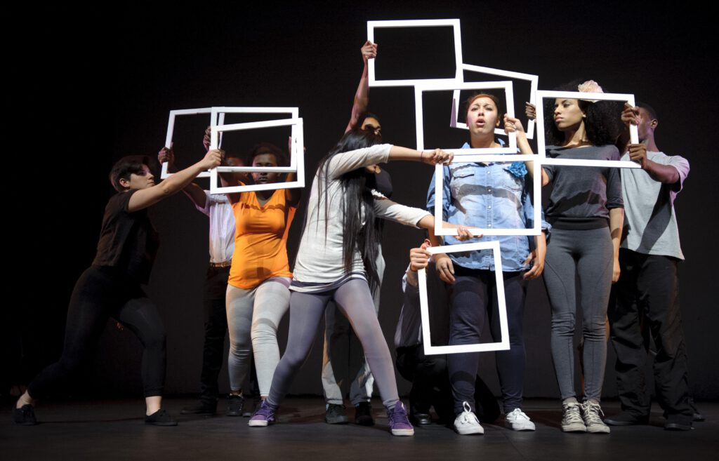 A group of actors hold picture frames over their faces