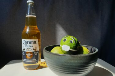 A bottle of Corona beer and a lime with eyes and a facemask