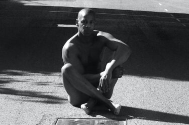 Black and white photo of artist Topher Campbell, seated