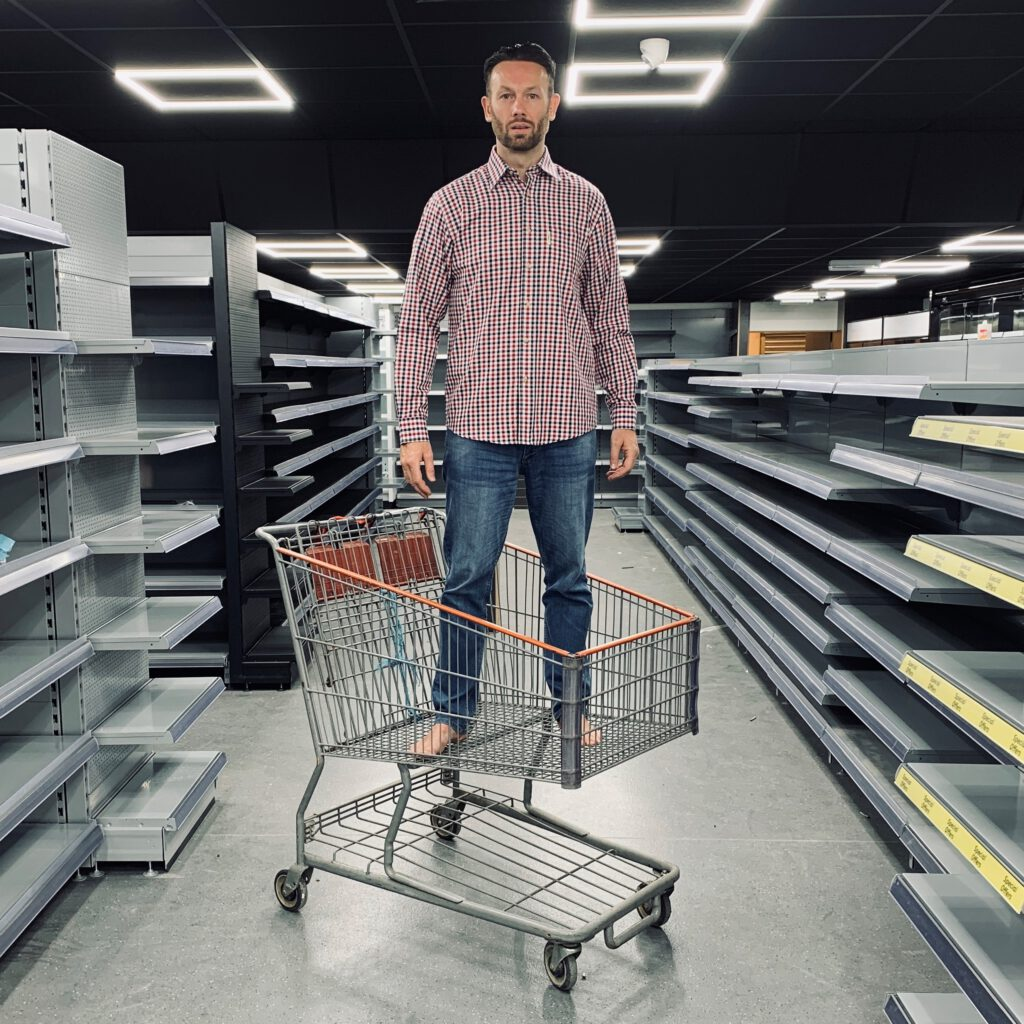 A man stands in a supermarket trolly surrounded by empty shelves.