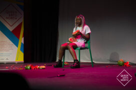 Artist Mandla Rae sits on stage, surrounded by broken watermelon