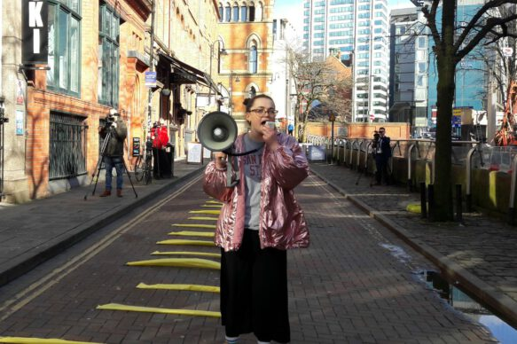Ali is stood on Canal Street in Manchester. She is wearing a pink jacket and is holding a loudspeaker.