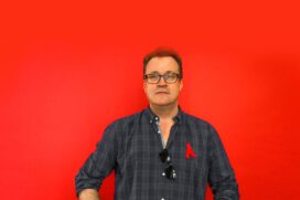 Russell T Davies stands against a red backdrop