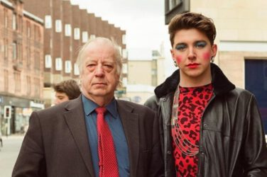 An older man in a suit and a person in makeup and a red print top