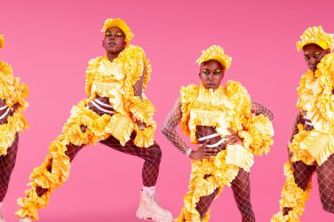Dancers dressed in yellow against a pink background