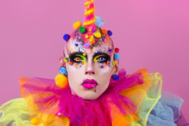 Artist Cheddar Gorgeous dressed as a rainbow-coloured clown with a pink unicorn horn