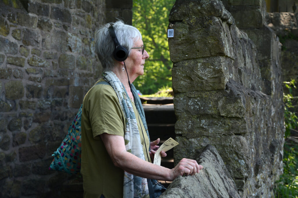 A woman stands in an outside area listening on headphones. From A Home for Grief Sound walk