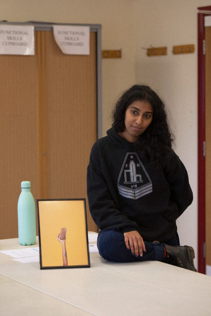Audrey Albert sits on a table with a water bottle to her left and artwork balanced next to her