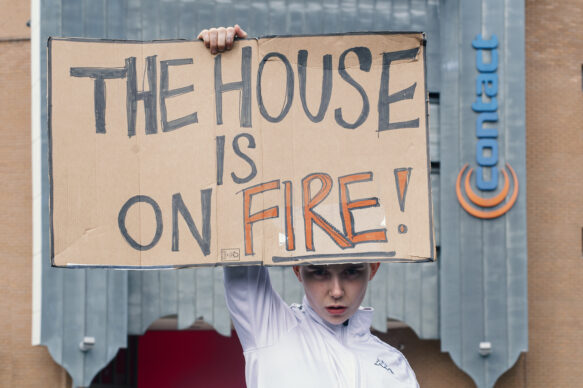A young person stands outside Contact, holding a paper sign with the words THE HOUSE IS ON FIRE written in pen