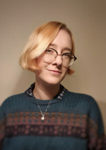 freelance facilitator and youth worker wearing blue and brown jumper and smart glasses with short blonde hair.