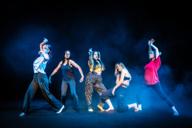 Five dancers pose on a theatre stage with blue haze
