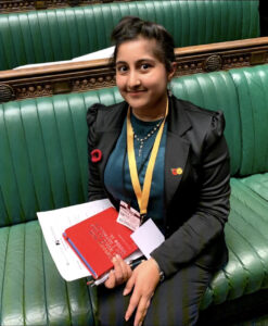 Climate activist Ishaa sitting in parliament on a green bench wearing a suit