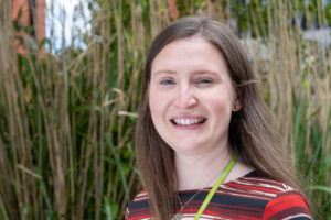 Climate Change Manager stands in front of long grass, wearing strip red and black shirt, green lanyard and long brown hair