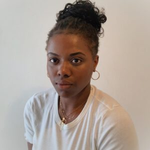 Multi-disciplinary artist working in theatre, film, and TV wearing a white top and hoop earrings with black hair in a bun.